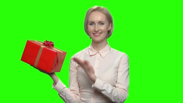 Žena ukazuje na červené krabičky.