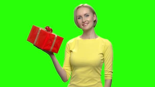 Gyönyörű érett nő a gazdaság piros ajándék doboz sárga pulóver.