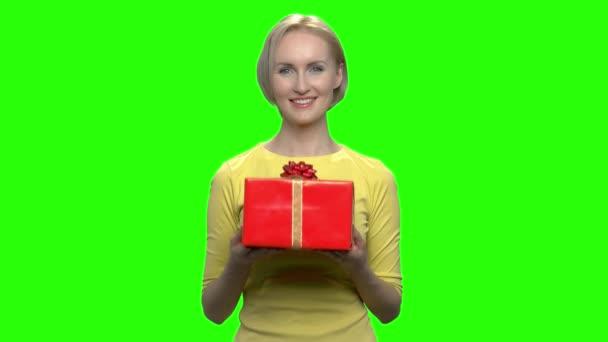 Szép nő, ami piros díszdobozban. Zöld hromakey háttér beírásához.