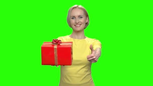 Happy středního věku žena s červené krabičky a palec nahoru.