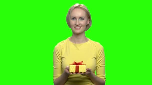 Krásná zralá žena držící žluté krabičky s oběma rukama.
