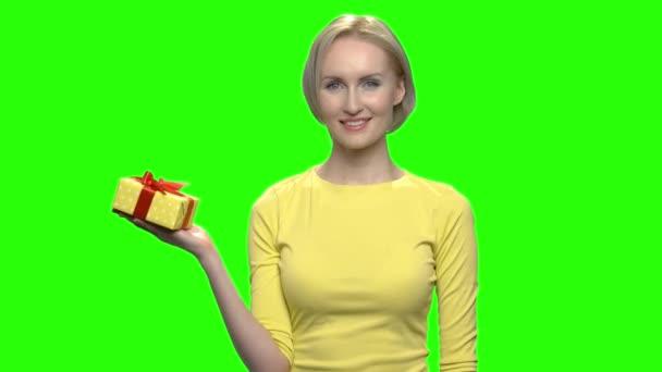 Érett nő gazdaság sárga ajándék doboz egy kézzel.