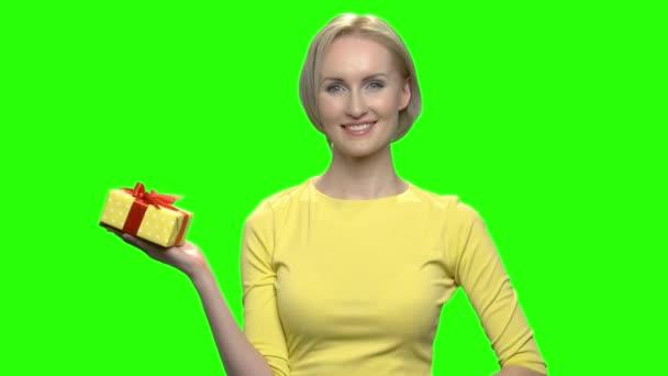 S úsměvem šťastná žena s pole žluté dárkové krabičky.