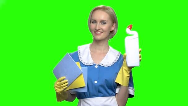 Frau mit Toilettenreiniger-Flasche und Servietten zum Reinigen.