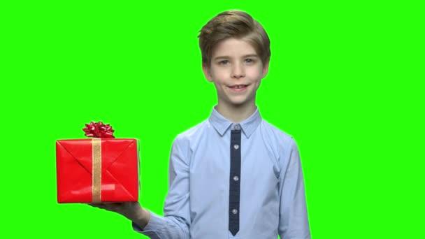 Roztomilý kavkazské chlapeček držící červená dárková krabička.
