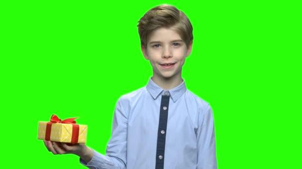 Pěkný dítě drží žluté Dárková krabice s červenou stužkou.