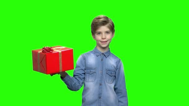 Junge in Jeansjacke mit roter Geschenkbox und erhobenem Zeigefinger.