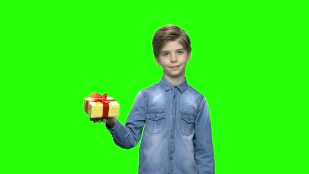 Aranyos kisfiú mutatva sárga ajándék doboz-val piros szalag.