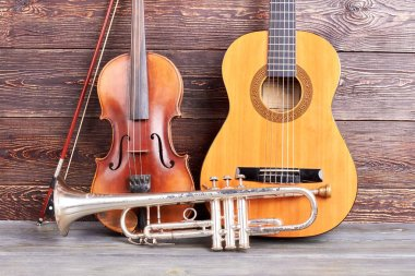 Old musical instruments on wooden background.