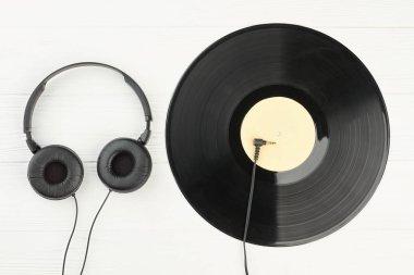 Vinyl record and headphones on white background.
