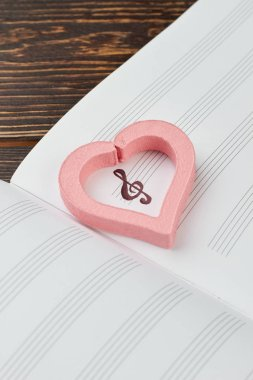 Pink heart on musical note book.