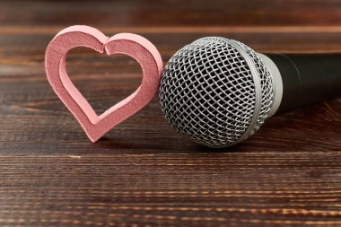 Microphone and heart on wooden background. Gray microphone and pink heart shaped decoration on brown wooden table. This is love song. For music lovers. stock vector