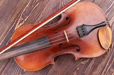 Brown violin on wooden table.