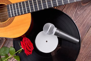 Guitar, vinyl record, microphone and rose.