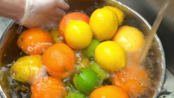 Hands washing fresh fruits.