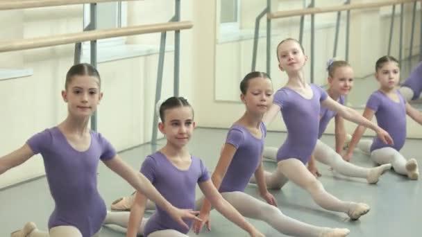 Group of ballet girls doing split at dance studio. Young ballerinas sitting on the floor on split. Classical ballet class. Dream of childhood.