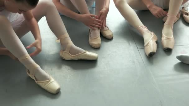 Close up little ballerinas tying their pointe shoes.