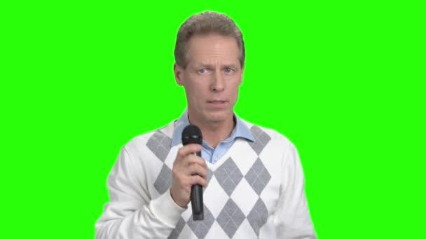 Komoly ember a mikrofon, zöld képernyő.