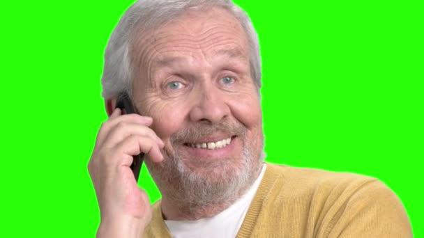 usmívající se muž mluví na mobilním telefonu.