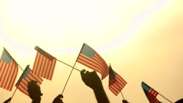 Close up American flags in peoples hands. Patriotic people raised USA flags to the evening sky. Concept of country Independence.