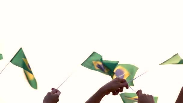 Back view people raising Brazilian flags.