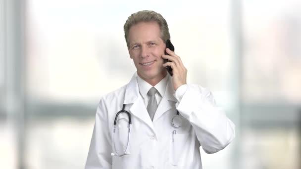 Středního věku kavkazské lékaře s mobilním telefonem.