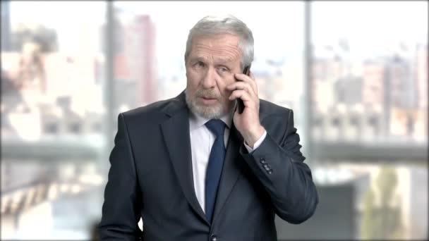 Bearded businessman talking on phone.