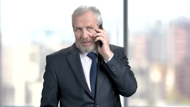 Confident mature businessman with mobile phone.