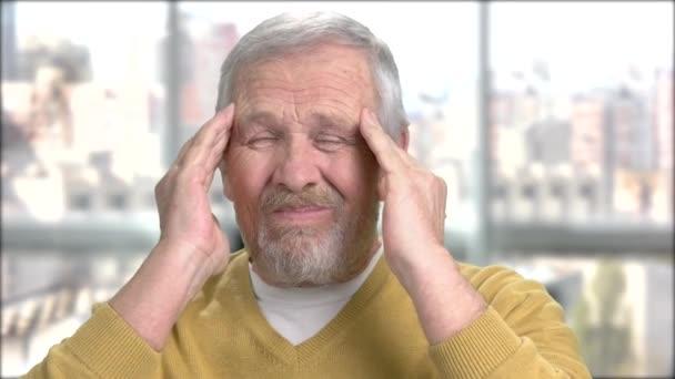 Uomo senior con il mal di testa terribile