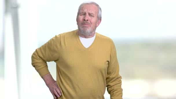 Elderly man is suffering from back pain.