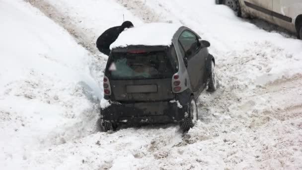 Řidič kopání auta uvízl ve sněhu.
