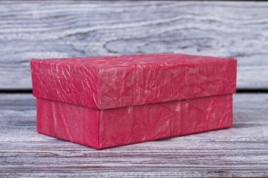Pink gift box on wooden background.