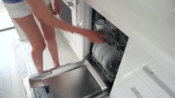 Frau holt sauberes Geschirr aus Spülmaschine.