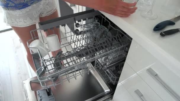 Frau Entladen der Spülmaschine zu Hause