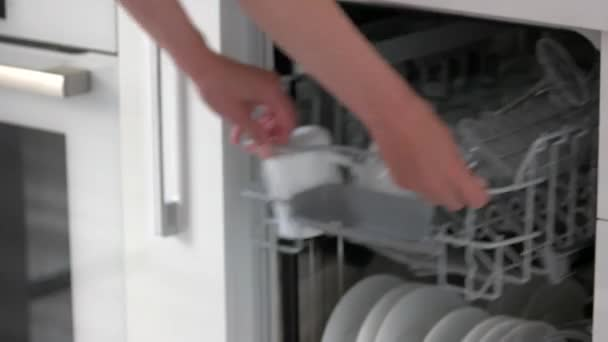 Female hands unloading dishwasher at home.