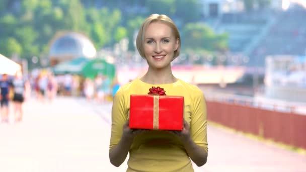 Žena dává krabičky na rozostřeného pozadí