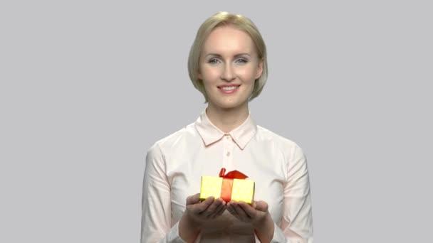 Mladá půvabná žena dává krabičky.