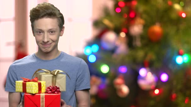 Chlapec dává dárkové krabice na rozmazané vánoční osvětlení.