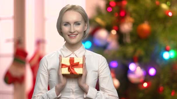 Žena držící krabičky na abstraktní Vánoční pozadí