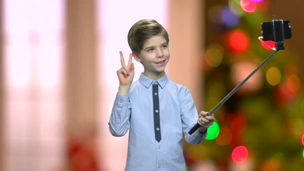 Cute boy using selfie stick.