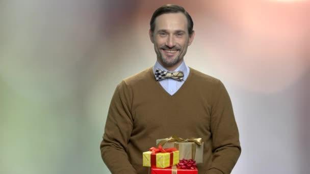 Vousatý muž dává dárkové krabice.