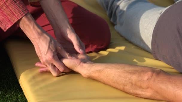 Relaxed man receiving hand massage outdoors.