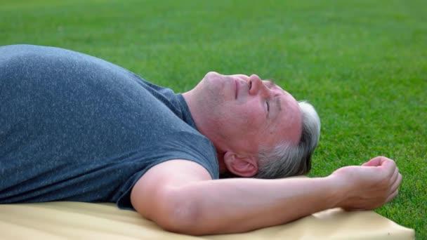 Uvolněný člověk dostává masáž na zelené trávě