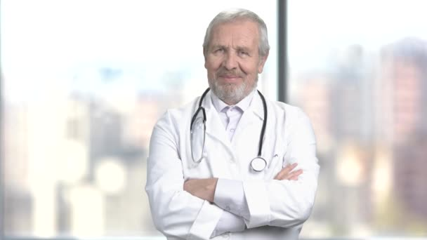 Elderly male doctor with crossed arms.