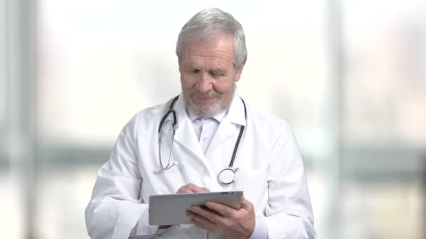 Smiling elderly doctor with pc tablet. Cheerful caucasian doctor using computer tablet on abstract blurred background.