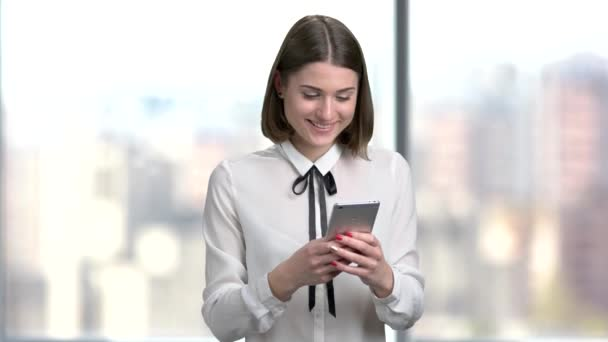 Young smiling woman using smartphone.