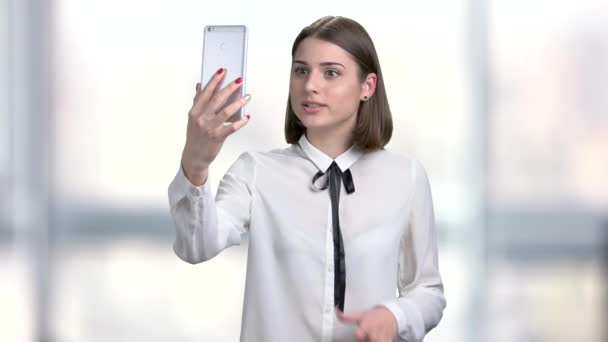 Young woman holding smartphone and talking.