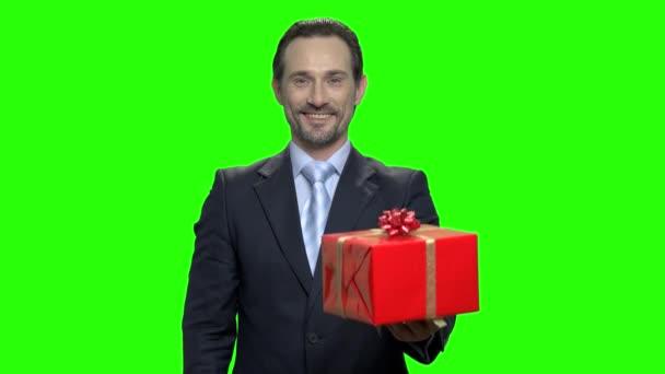 Usmívající se atraktivní zralá obchodní muž dává vám dárek.
