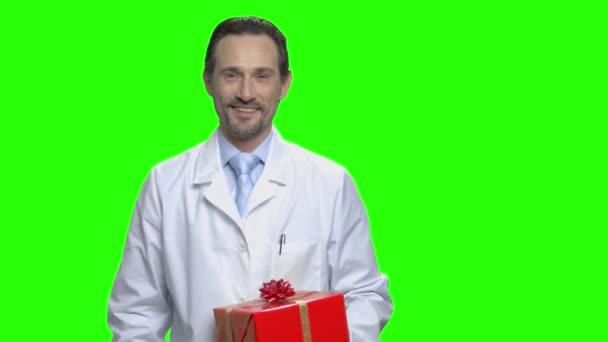 Férfi orvos jelen díszdobozban és hüvelykujjával felfelé portréja.
