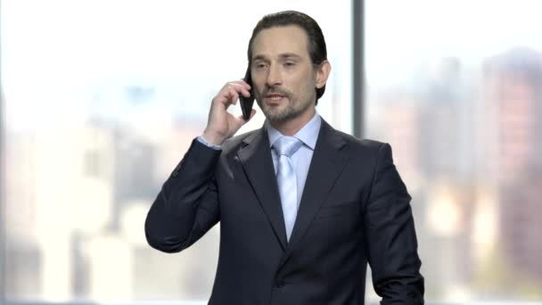 Attractive businessman talking on cell phone. Handsome caucasian entrepreneur using mobile phone on blurred office window background. Business people and technology.